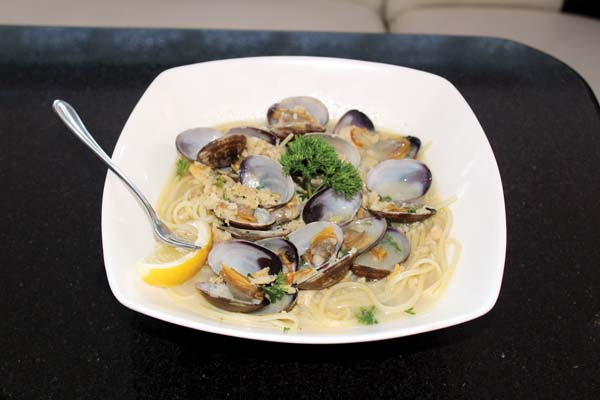 Clams are sauteed with garlic, wine and butter and infused in a spicy natural clam broth over a bed of linguine. The Maui News / CARLA TRACY photo