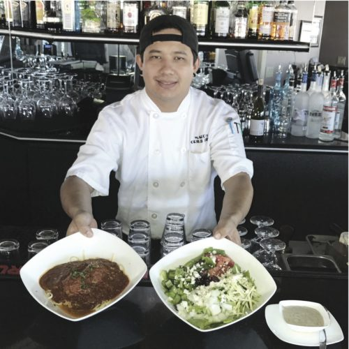 Marco's new Chef Cory Moscutt showcases two of the house specialties, linguine and meatballs and Greek salad.  The Maui News / CARLA TRACY photo