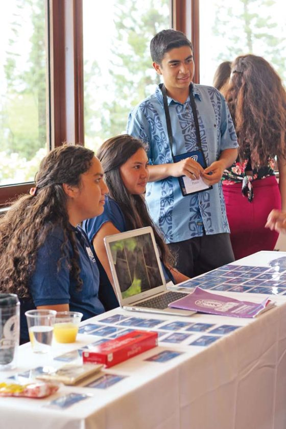 Kamehameha Schools Maui seniors Ariana Hurdle (from left), Kailani Kealoha and Austin Peters meet with visitors to their booth showcasing Ola Na Iwi, an on-campus club that promotes Hawaiian language and culture.  The Maui News / COLLEEN UECHI photo