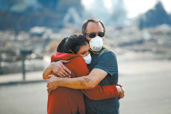 "Howard Lasker comforts daughter Gabrielle in Santa Rosa, Calif., on Sunday. With the winds dying down, fire officials said Sunday that they have apparently ""turned a corner"" against the wildfires that have devastated wine country and other parts of California over the past week. AP photo"