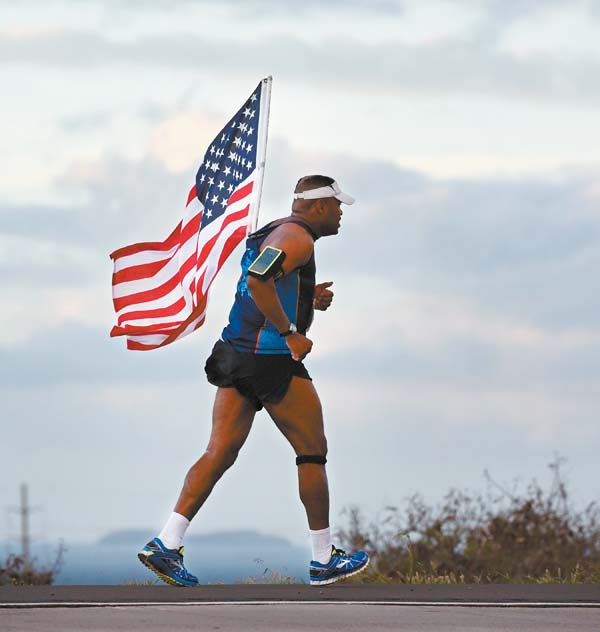 Melvin Coleman of North Carolina carries the American flag toward Maalaea — he said it was his eighth time running the race with the Stars and Stripes. The Maui News / MATTHEW THAYER photo