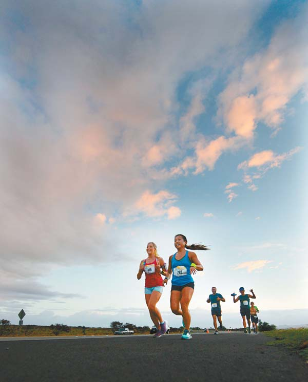 The sun rises over Joy Welker (left) of Oregon, Joanna Meyer of Arizona and other Maui Marathon runners. The Maui News / MATTHEW THAYER photo