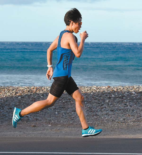 Tetsuya Yoroizaka grabs a drink while running through Olowalu on the way to winning the men's title in 2:43:21. The Maui News / MATTHEW THAYER photo