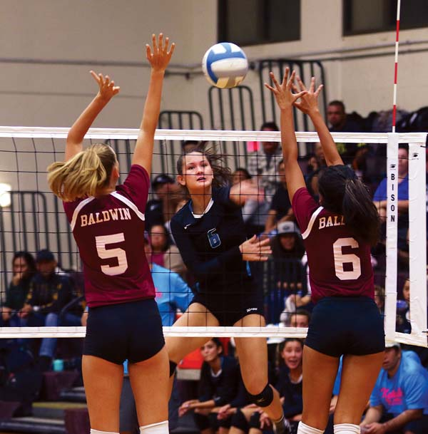 Nina Macphetridge of King Kekaulike High School hits the ball between the block of Baldwin's Anela Bechert (left) and Siena DeCambra in the first set of Na Alii's victory over the Bears in a Maui Interscholastic League Division I tournament semifinal Tuesday night. The Maui News / CHRIS SUGIDONO photo