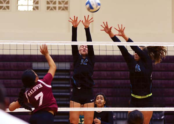 King Kekaulike's Daniella Wittenberg (12) and Annika Stammberger try to block a shot by Baldwin's Avei Silifaiva in the first set Tuesday. The Maui News / CHRIS SUGIDONO photo