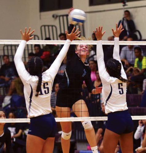 Chandler Cowell of King Kekaulike High School hits against Kamehameha Maui's Logan Spencer (left) and Aliah Ayau in the second set Friday. -- The Maui News / CHRIS SUGIDONO photo