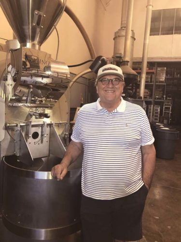 "Nicky ""Beans"" Matichyn stands by a commercial machine at Maui Coffee Roasters in Kahului. -- The Maui News / CARLA TRACY photo"