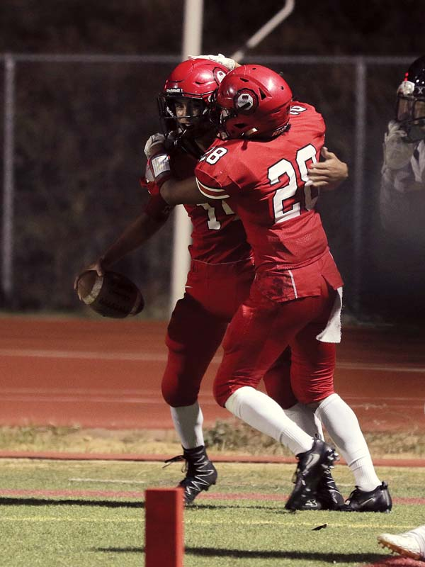 Lahainaluna High School's Mystic Kauhaahaa celebrates with Derek Perez after scoring on a punt return in the first quarter of the Lunas' 49-7 win over Kamehameha Maui on Saturday at Sue Cooley Stadium. -- The Maui News / CHRIS SUGIDONO photo