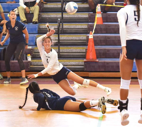 Talia Leauanae of Kamehameha Schools Maui dives over teammate Inez Garcia to keep a ball in play during the fifth set of the Warriors' 12-25, 25-22, 25-23, 25-27, 15-12 win over King Kekaulike on Saturday in the Maui Interscholastic League Division I championship match at Jon Garcia Gym. -- The Maui News / MATTHEW THAYER photo