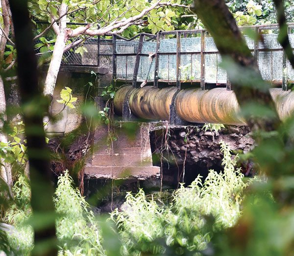 The concrete foundation supporting the end of a footbridge and irrigation pipe spanning Wailuku River is undermined in this photo taken Wednesday morning. The support was damaged after heavy rains early Tuesday morning that caused the river to swell. The Maui News MATTHEW THAYER photo