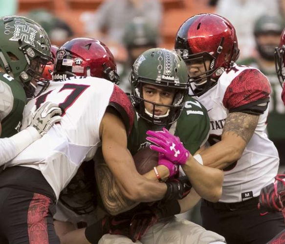 Hawaii's Keelan Ewaliko is tackled by San Diego State's Ron Smith (17) and Israel Cabrera during the Rainbow Warriors' 28-7 loss to the Aztecs on Saturday. -- AP photo