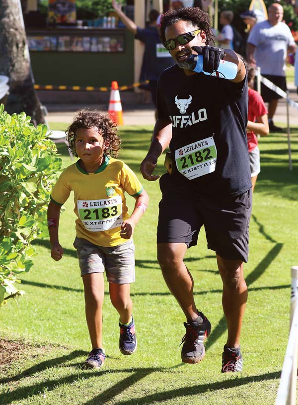 Bo Monteiro points to the finish line for his son, Promitto, in the Leilani's 3.3K. -- The Maui News / CHRIS SUGIDONO photo