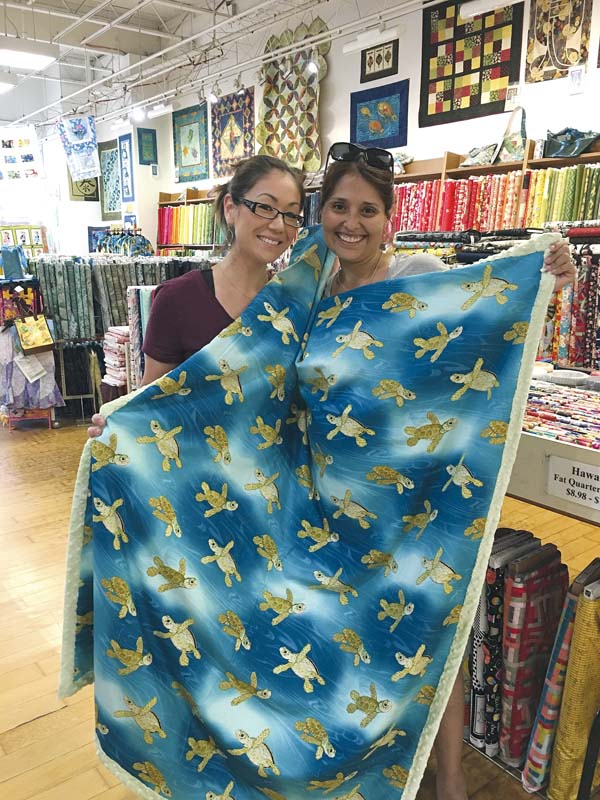 Patricia Huntley (left in photo), owner of Hapa Maui Designs, shows off a custom-made, cotton-and-minky blanket. The fabric is from Maui fabric designer Mark Hordyszynski.