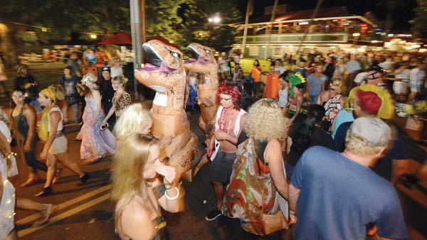 A pair of velociraptors trots in formation through the crowd on Front Street in Lahaina on Halloween night. The Maui News / MATTHEW THAYER photo
