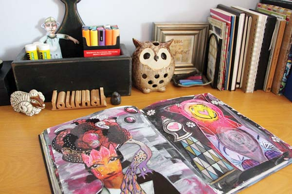 This photo show a mixed-media journal on a desk outfitted for artistic endeavors. -- Photo via AP