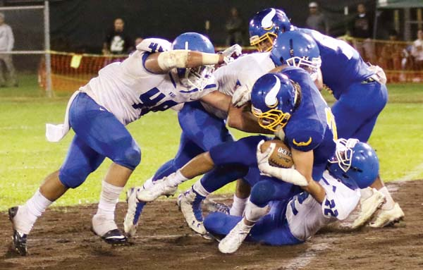 Hilo running back Kahale Huddleston is brought down by Maui High defenders Saturday night. -- Hawaii Tribune-Herald / TIM WRIGHT photo