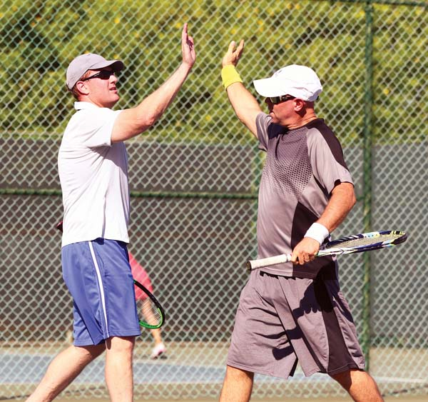 Jonathan Yudis (right) of Kula high-fives Ben Falit of Makawao during their 7-6, 6-0 victory over Ken Christopher and Kitt Knisley in a men's 7.0 match. -- The Maui News / CHRIS SUGIDONO photo