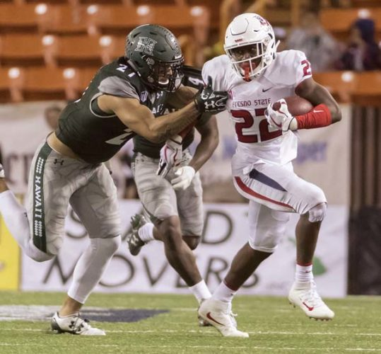 Hawaii's Solomon Matautia tries to bring down Fresno State's Jordan Mims during the first half of the Rainbow Warriors' 31-21 loss to the Bulldogs on Saturday at Aloha Stadium. -- AP photo