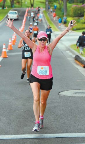 Paula Stockman of Vancouver, British Columbia, raises her arms as she crosses the finish line Saturday in the Day of Hope 5K in Wailea. The Maui News / MATTHEW THAYER photo