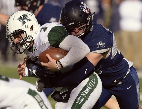 Utah State's Chase Christiansen sacks Hawaii quarterback Dru Brown during the Aggies' 38-0 win over the Rainbow Warriors on Saturday. -- The Herald Journal via AP / ELI LUCERO photo