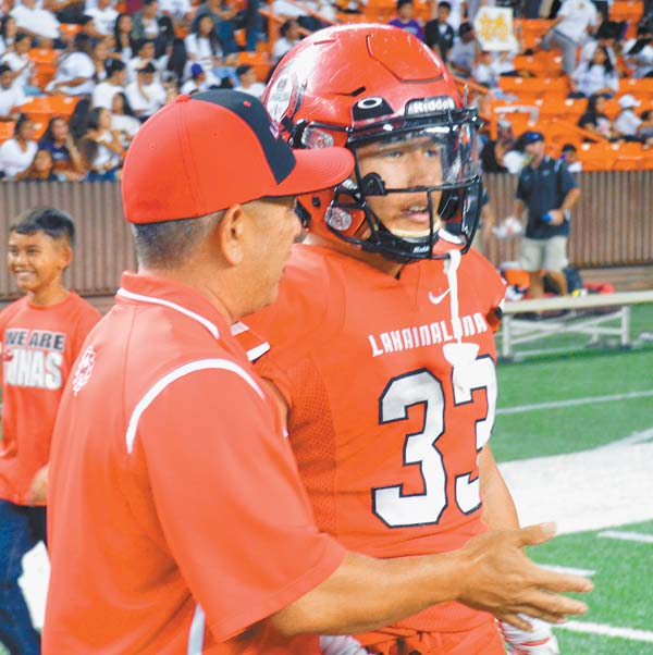 Lahainaluna assistant coach Joey Tihada talks with his son Joshua, who scored five touchdowns Saturday and had eight in two postseason games. The Maui News / ROBERT COLLIAS photo