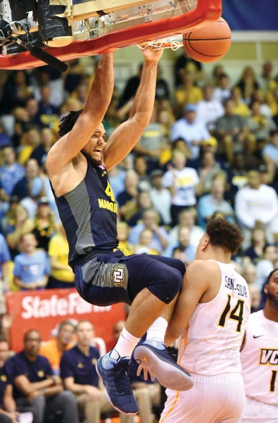 Marquette's Theo John dunks over VCU's Marcus Santos-Silva in the second half.