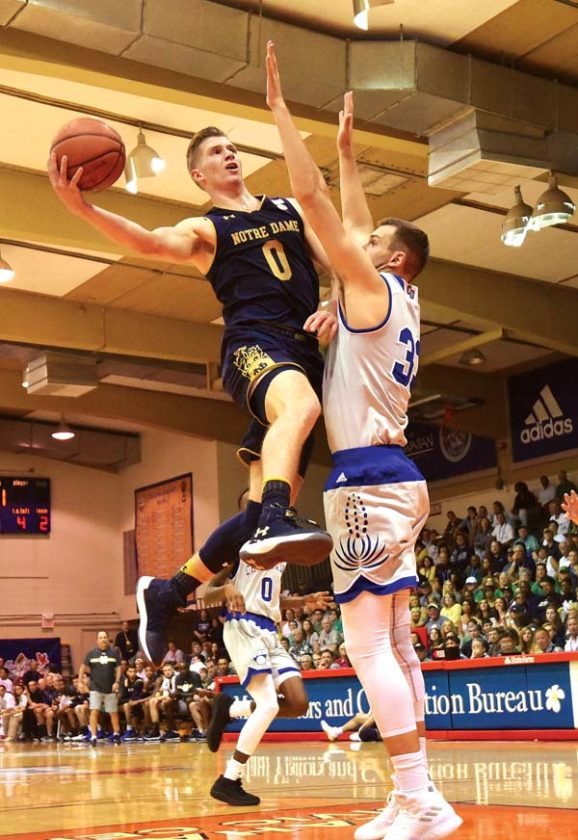 Notre Dame's Rex Pflueger drives on Chaminade's Braden Koelliker in the first half of an 83-56 win for the Fighting Irish on Monday. The Maui News / MATTHEW THAYER photos