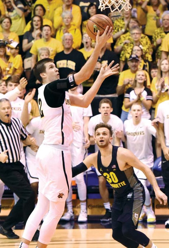 The Shockers' Austin Reaves goes up for a layup in front of the Golden Eagles' Andrew Rowsey.