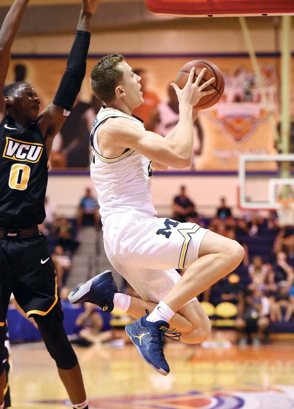 Michigan's Duncan Robinson goes up for a shot in front of Virginia Commonwealth's  De'Riante Jenkins during the second half of the Wolverines' 68-60 victory over the Rams on Wednesday. The Maui News / MATTHEW THAYER photo