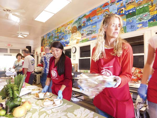 Volunteers Kristinia Alger (left) and Wendy Laurel serve up plates of turkey, mashed potatoes, stuffing and yams on Thursday at the annual Thanksgiving Feast at King Kamehameha III Elementary School in Lahaina.