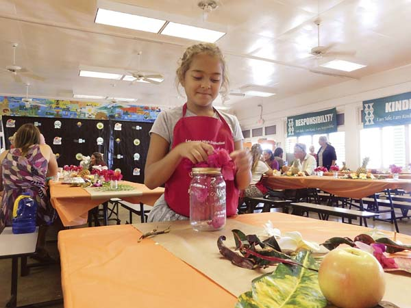 Ten-year-old Faith May arranges flowers while volunteering at the Thanksgiving Feast at King Kamehameha III Elementary School in Lahaina on Thursday. The Maui News / LIILA FUJIMOTO photo