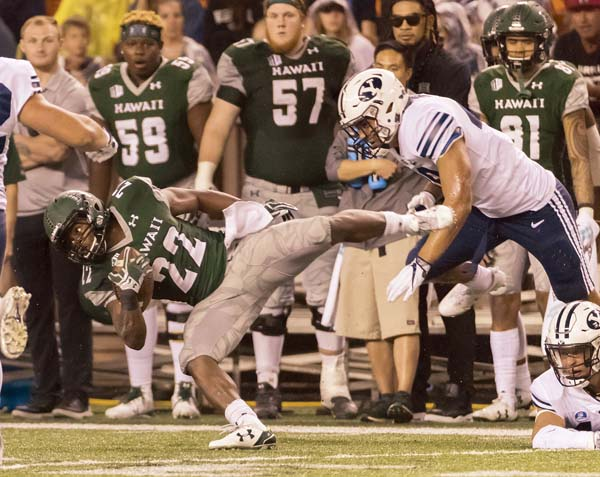 Hawaii running back Diocemy Saint Juste dives to gain more yards during the Rainbow Warriors' 30-20 loss to BYU on Saturday. -- AP photo