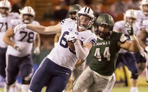 BYU tight end Matt Bushman runs with the ball while Hawaii's Russell Williams Jr. gives chase during the third quarter Saturday. -- AP photo