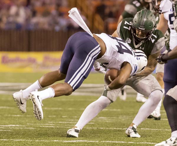 The Rainbow Warriors' Solomon Matautia tackles the Cougars' Riley Burt by grabbing his face mask in the fourth quarter. -- AP photo