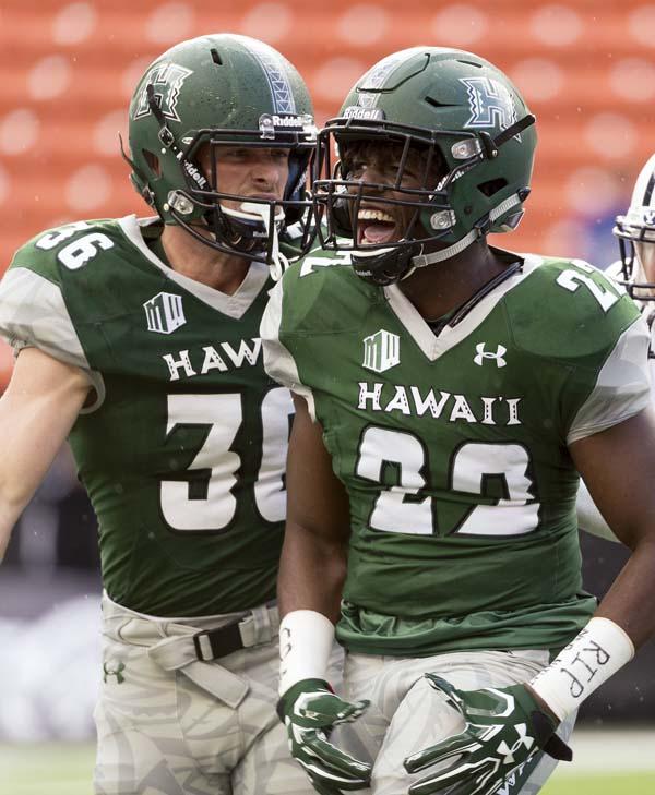 Hawaii's Ben Scruton (left) and Ikem Okeke celebrate a hard tackle in the first quarter. -- AP photo