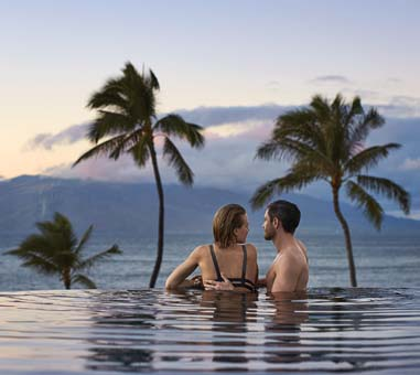 An adult infinity pool features  underwater music along with views of the Neighbor Islands, the ocean and  West Maui Mountains. -- Four Seasons photo