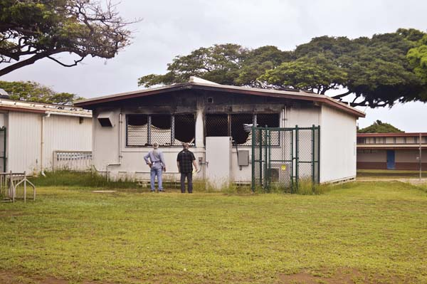 Kahului Elementary School custodian Clifford Prais (left) assesses the damage to a portable classroom building at the school alongside Maui Police Department Detective Christopher Schmitt on Monday morning at the campus. A fire Friday night, classified as an arson, burned six classrooms. School is closed for students until Thursday. The Maui News / MELISSA TANJI photo