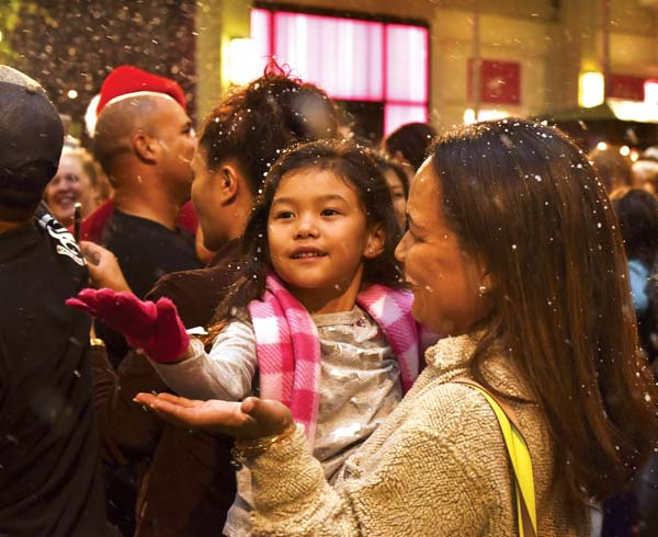 "Yukie Ruidas, 4, wears her winter gloves while catching ""snow"" with mom Kekane Ruidas during one of last year's ""Let it Snow"" events at the Queen Ka'ahumanu Center. The Maui News / MATTHEW THAYER photos"