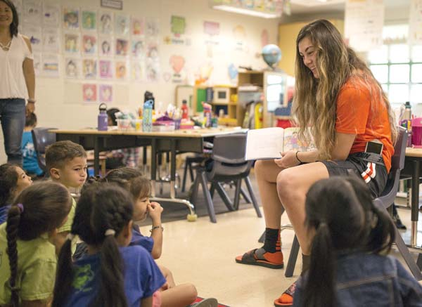 Oregon State forward Janessa Thropay reads to students at Pomaikai Elementary School on Thursday. Nevada visited Kamalii Elementary, while Utah State visited Kihei Elementary — Montana State was unable to visit a school due to a flight conflict. Brand and Brush photo