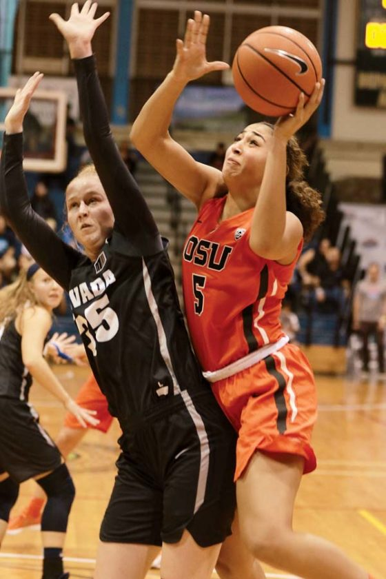 The Beavers' Taya Corosdale makes a basket as she's fouled by Nevada's Kristin Dearth in the first quarter. - The Maui News / CHRIS SUGIDONO photo