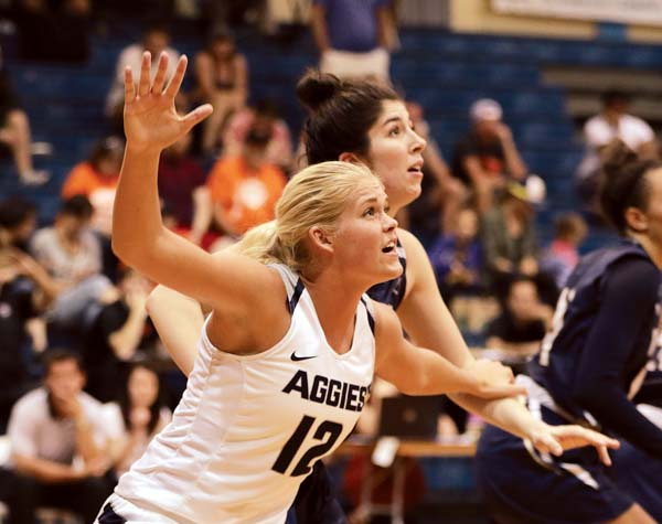 The Aggies' Hailey Bassett calls for the ball in front of the Bobcats' Madeline Smith in the fourth quarter. - The Maui News / CHRIS SUGIDONO photo