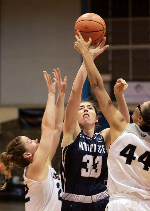 Smith tries to shoot over Utah State's Deja Mason (right) and Rachel Brewster in the third quarter. - The Maui News / CHRIS SUGIDONO photo