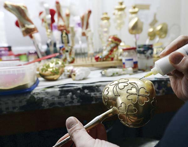 A painter decorates a gold heart with paint. -- APphoto