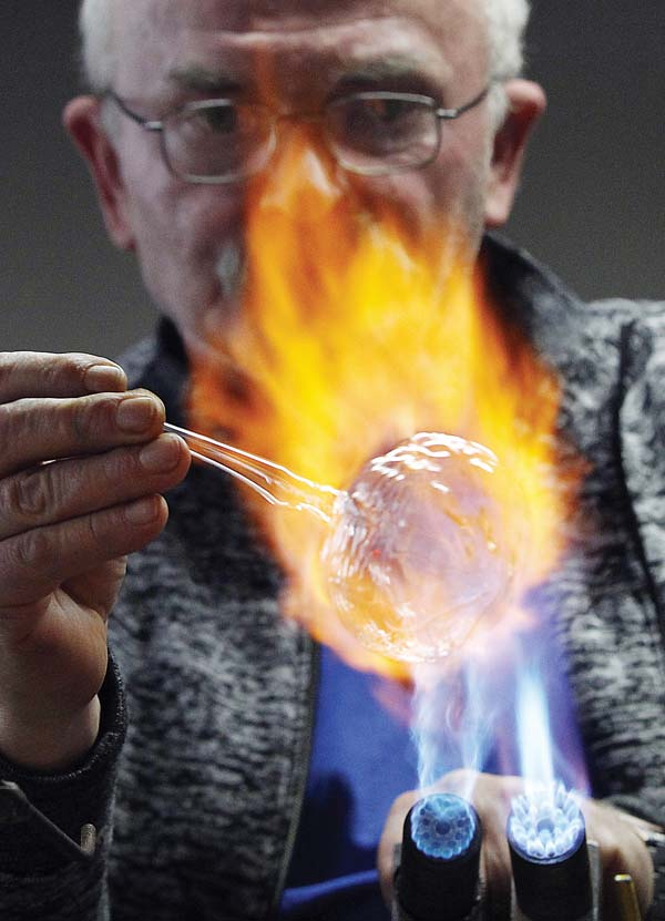 Ryszard Baran shapes hot glass into an ornament. -- APphoto