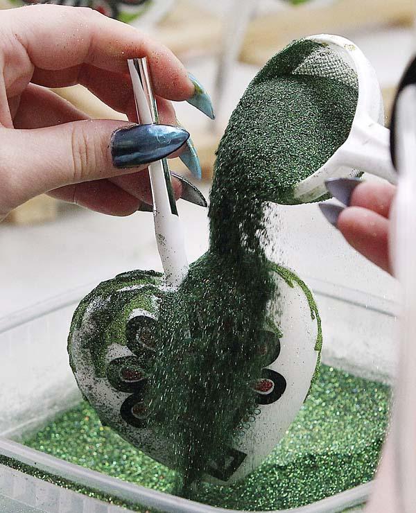 A decorator adds glitter to a blown ornament. -- APphoto