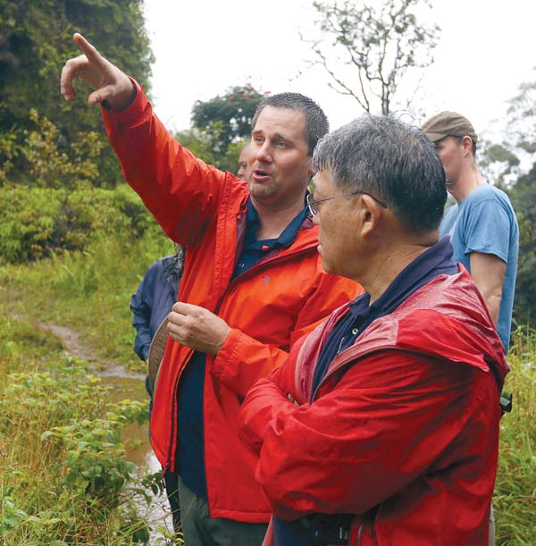 A state Department of Land and Natural Resources hydrologist, who declined to be identified, points out parts of the Koolau Ditch to state Commission on Water Resource Management member Keith Kawaoka on Wednesday in East Maui. - The Maui News / CHRIS SUGIDONO photo