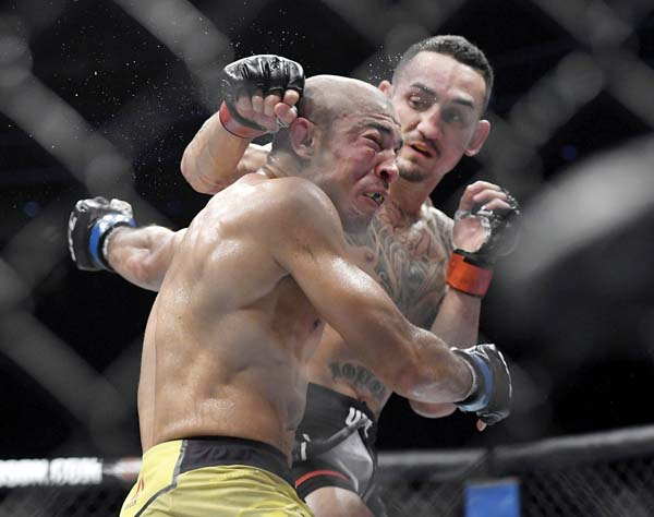 Max Holloway punches Jose Aldo during the third round of their featherweight title fight Saturday at UFC 218. -- AP photo