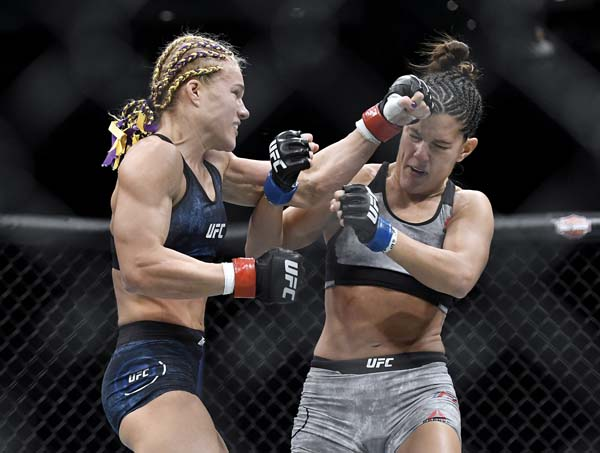 Felice Herrig (left) and Cortney Casey exchange punches in the first round of their strawweight fight Saturday. -- AP photo