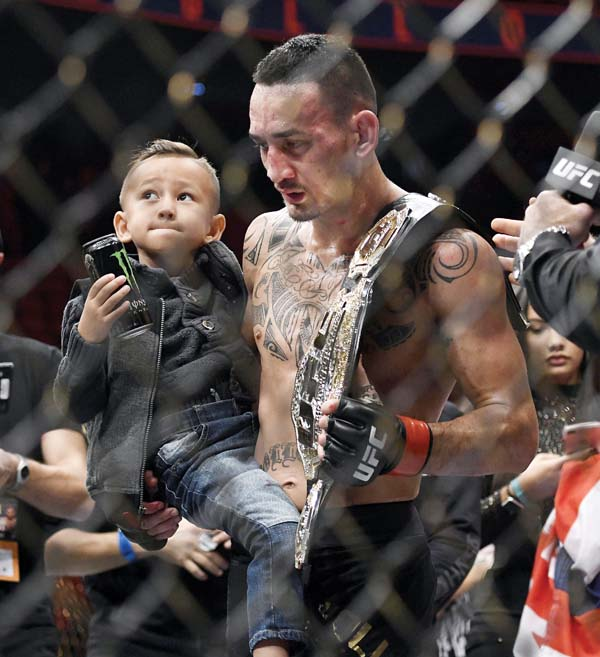 Max Holloway holds his son, Rush, after defeating Jose Aldo on Saturday. -- AP photo