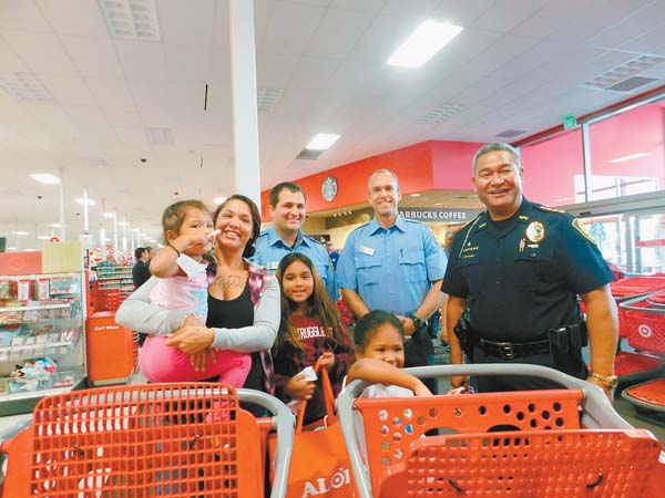 Tiare Abraham, holding 3-year-old Hina'ea, and daughters Ayanna, 9, and Kawai, 6, leave Target after getting help from police recruits Michael Russell and Scott McCalister and Police Chief Tivoli Faaumu during the Shop With a Cop event Sunday morning.